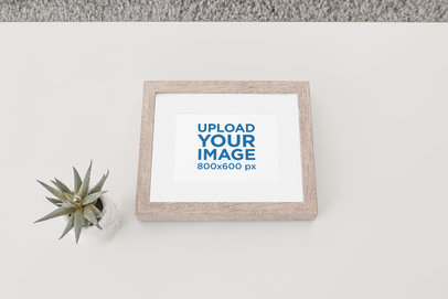 Wooden Picture Frame Mockup Placed Against a Flat Surface by an Indoor Plant 616-el