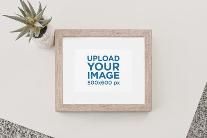 Mockup of a Wooden Picture Frame on a Plain Surface with a Desert Plant 621-el