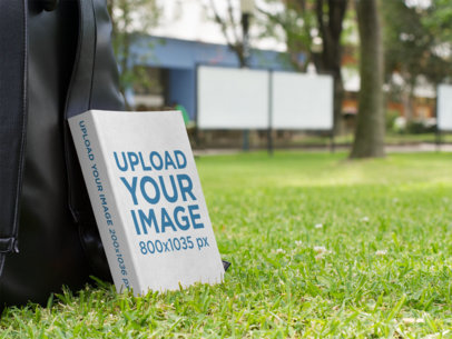 Ebook Mockup Leaning Against a Backpack in a Garden a9889