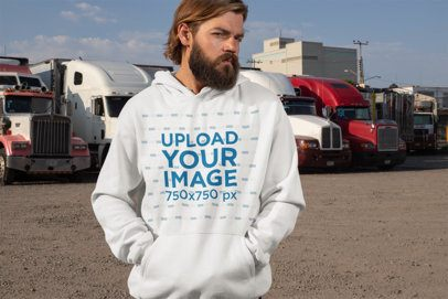 Pullover Hoodie Mockup of a Man Posing with Trucks in the Background 29493