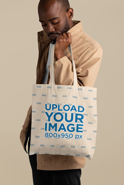 Mockup of a Bald Man Holding a Sublimated Tote Bag at a Studio 29450
