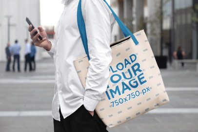 Mockup of a Man Carrying a Tote Bag and Checking His Phone 29418