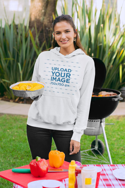 Hoodie Mockup of a Woman at a BBQ Party Holding a Casserole with Boiled Corn 29706