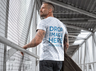 Back Shot of a Man Wearing a Sublimated Tee Mockup Walking on a Bridge a9357b