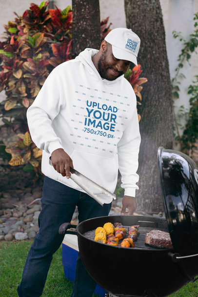 Pullover Hoodie Mockup of a Man Wearing a Dad Hat Grilling Food 29712