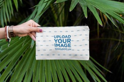 Mockup of a Hand Holding a Pouch Against Some Palm Leaves 29969