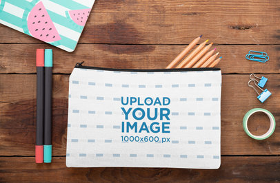Mockup of a Pouch Laying on a Wooden Surface with Stationery Tools