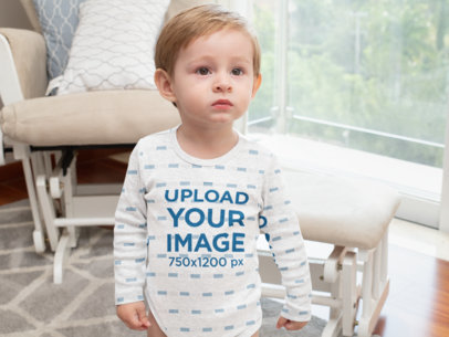 Heather Mockup of a Little Boy Wearing a Long Sleeve Onesie in a Living Room