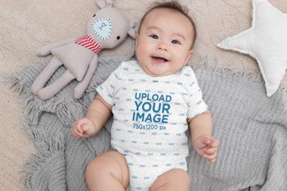 Heather Onesie Mockup of a Baby Boy Lying on Cozy Blankets 30041