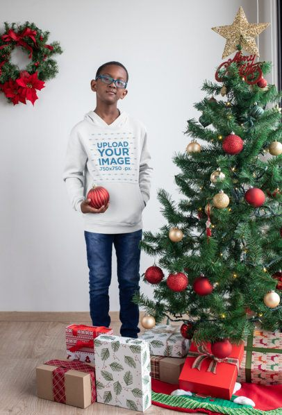 Pullover Hoodie Mockup Featuring a Kid Holding a Sphere by a Christmas Tree 30356