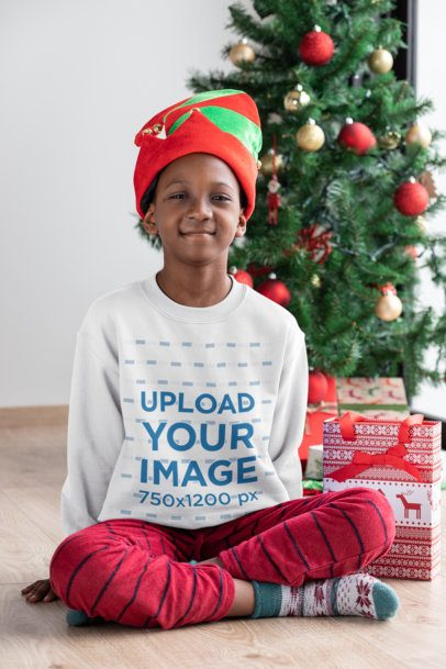 Mockup of a Kid with a Crewneck Sweatshirt Sitting Next to a Christmas Tree 30358