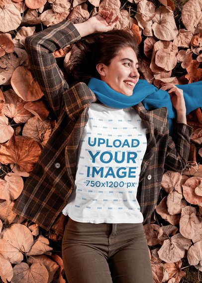 T-Shirt Mockup of a Woman Lying on Autumn Leaves 30108