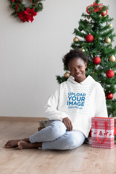 Mockup of a Woman with a Hoodie Sitting Next to a Christmas Tree 30350