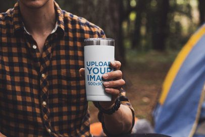 Mockup of a Man Holding a Travel Mug at a Campsite 30488