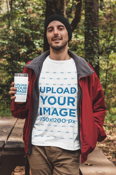 T-Shirt Mockup Featuring a Man Holding a 20 oz Travel Mug in the Woods 30486