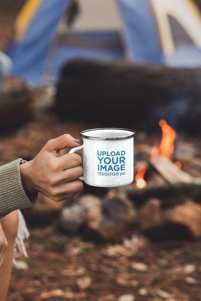 Mockup of a Woman Holding a 12 oz Enamel Mug by a Campfire 30504