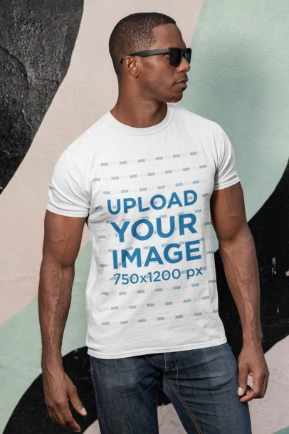 Mockup of a Man with Sunglasses Wearing a Customizable T-Shirt Against a Painted Wall 30447
