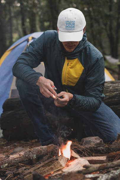 Mockup of a Man with a Dad Hat Lighting a Fire 30508