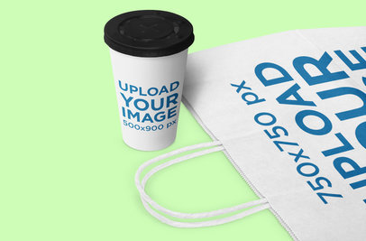 Mockup Featuring a Coffee Cup Standing Next to a Gift Bag 1071-el