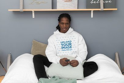 Pullover Hoodie Mockup Featuring a Man Sitting on His Bed 30321