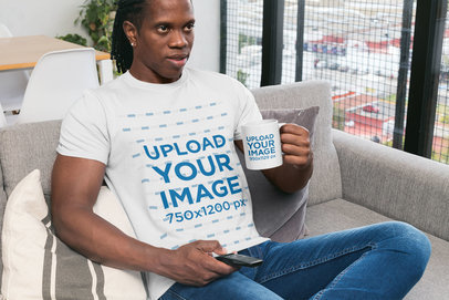 T-Shirt Mockup of a Man Holding an 11 oz Mug Sitting at Home 30312