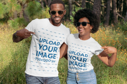 Mockup of a Young Couple Pointing at Their T-Shirts in a Nature Setting