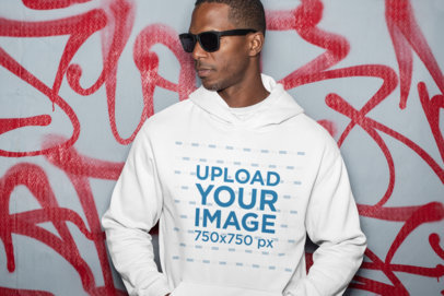 Hoodie Mockup Featuring a Man with Sunglasses by a Graffiti Wall 30458
