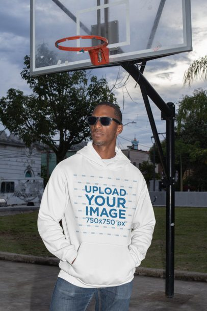 Mockup of a Fashionable Man Wearing a Pullover Hoodie at a Basketball Court 30460