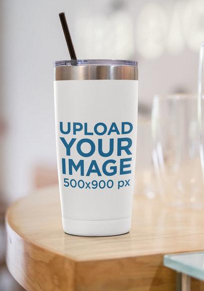 Mockup of a 20 oz Travel Mug Placed by a Glass 30420
