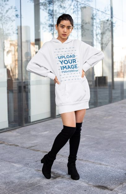 Mockup of a Woman with a Hoodie Dress Posing in Front of a Glass Building 30517