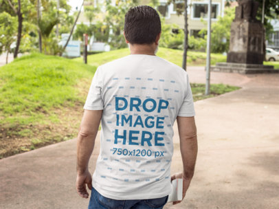 Back of a Man Carrying a Book Wearing a T-Shirt Mockup at the Park a11314b