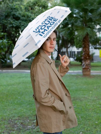 Mockup of a Stylish Man Holding an Umbrella by a Park 30723