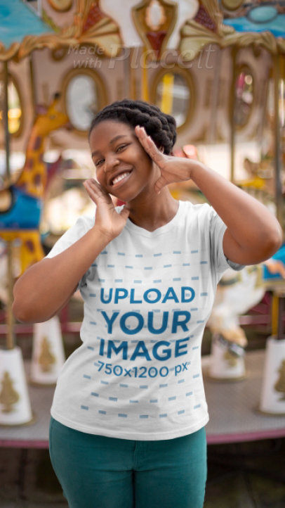T-Shirt Video Featuring a Joyful Woman Posing by a Carousel