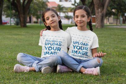 T-Shirt Mockup of Twin Girls Sitting on the Grass 30706