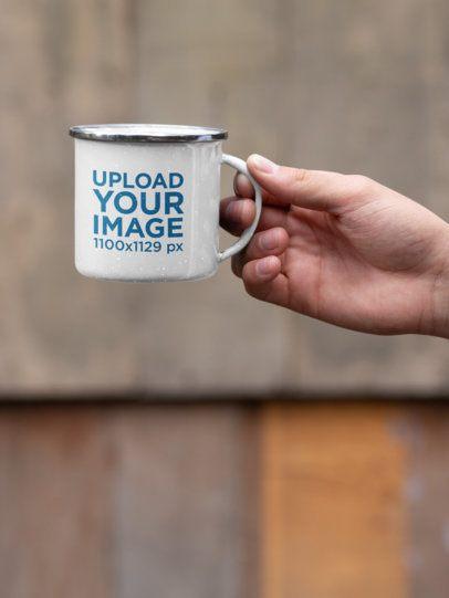 Mockup Featuring a Hand Holding a 12 oz Enamel Mug with a Silver Rim 30816