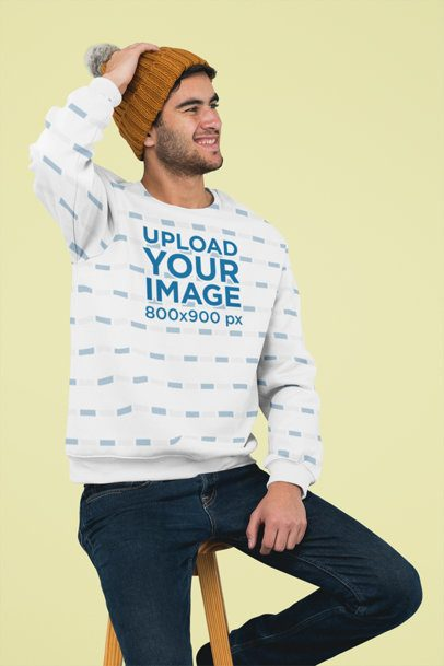 Sublimated Crewneck Sweatshirt Mockup Featuring a Man Sitting on a Stool at a Studio 31256
