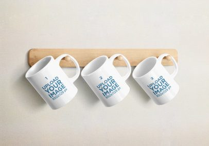 Mockup Featuring Three 11 Oz Coffee Mugs Hanging From a Wooden Rack 2374-el1