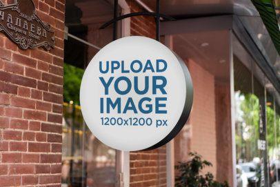 Mockup of a Circular Sign by a Brick-Wall Store 2220-el1