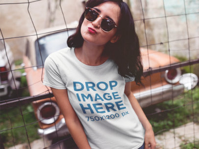Trendy Girl With Sunglasses Wearing a Tee Against a Fence a11825a