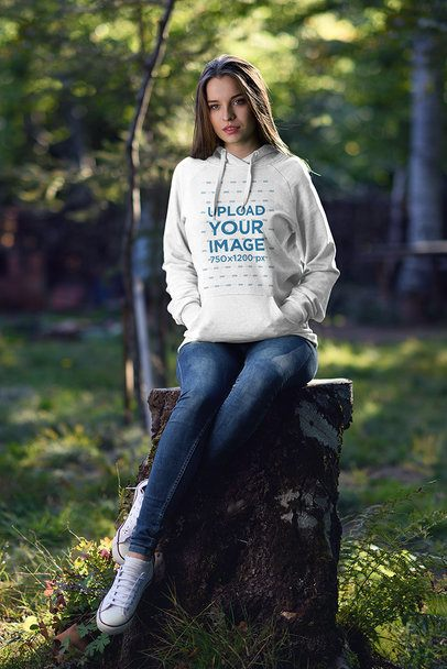 Mockup of a Woman Wearing a Hoodie While Sitting on a Lodge in the Woods 2794-el1