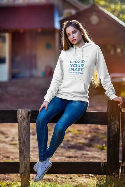 Mockup of a Woman Wearing a Pullover Hoodie and Sitting on a Rustic Wooden Fence 2795-el1