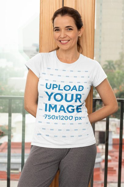 T-Shirt Mockup Featuring a Middle-Aged Woman Standing Against a Balcony Door 31606