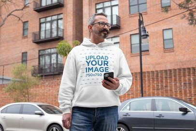 Pullover Hoodie Mockup of a Middle-Aged Man Holding His Phone in the Street 31717