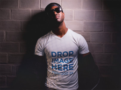 V-Neck T-Shirt Mockup of a Black Man Against a Wall Wearing Sunglasses a12157