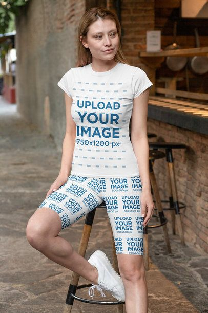T-Shirt Mockup of a Woman Wearing Bike Shorts Outside a Restaurant 31516