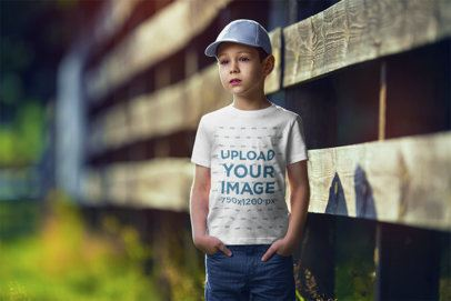 Mockup of a Boy Wearing a Customizable T-Shirt and Standing by a Wooden Fence 2919-el1