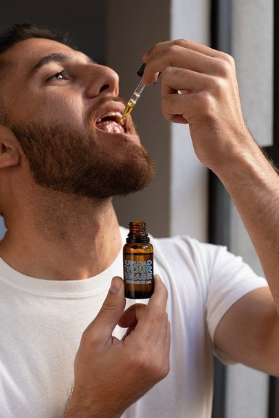 Dropper Bottle Mockup of a Man Taking CBD Oil 32104