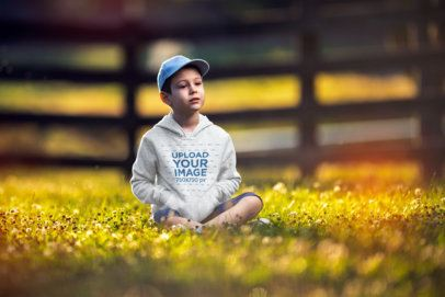 Hoodie Mockup of a Kid Sitting on the Grass 2931-el1