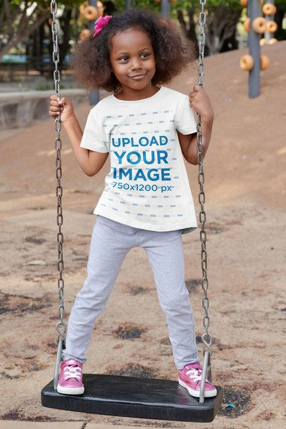 T-Shirt Mockup of a Playful Girl Standing on a Swing 32179