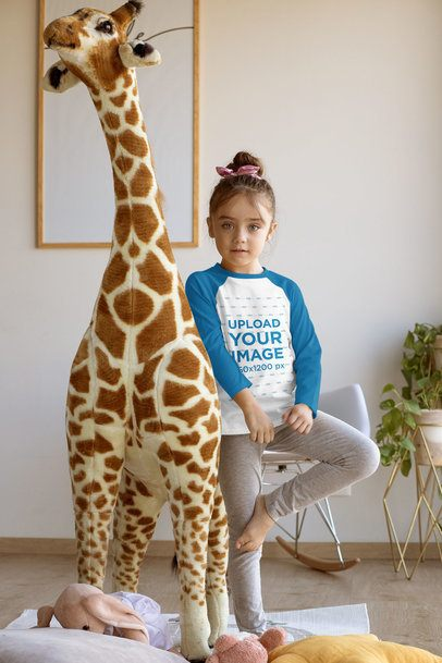 Raglan T-Shirt Mockup Featuring a Little Girl Standing by a Big Stuffed Giraffe 31688
